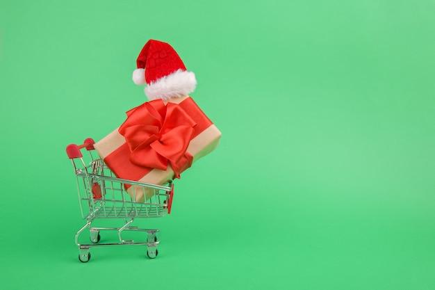 Caixa de conceito de compras de natal online com um presente e uma fita verde em um mini carrinho de compras ou carrinho ao lado de um