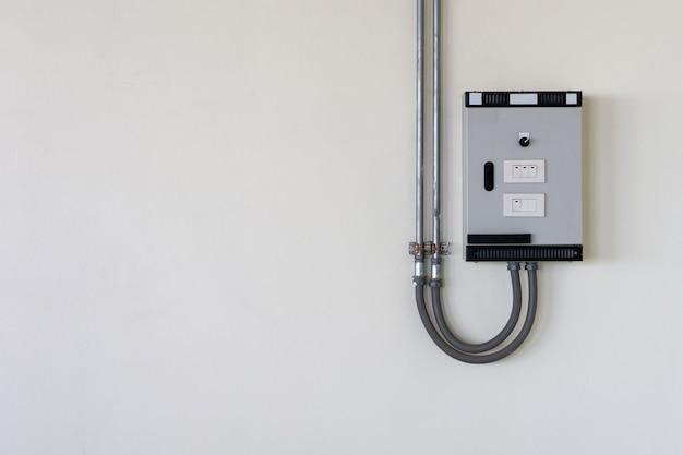 Caixa de controle elétrico com tubo de cabo na parede.
