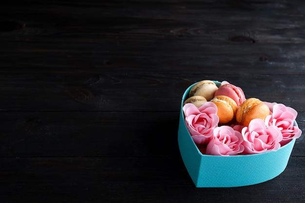 Caixa de coração azul com macaroons e rose no fundo escuro de madeira, copie o espaço