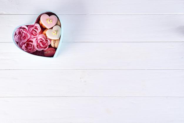 Caixa de coração com biscoitos e rose em fundo branco de madeira, dia dos namorados