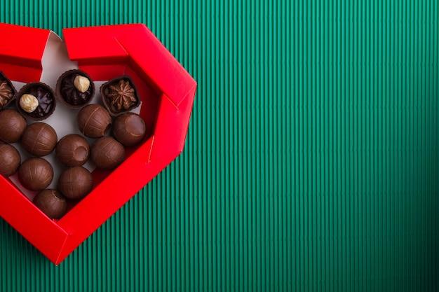 Caixa de coração com bombons de chocolate e espaço de cópia. vista superior plana lay.