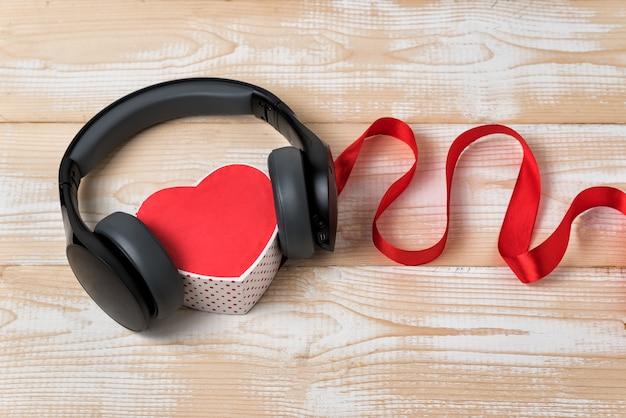 Caixa de coração com fones de ouvido estéreo e fita vermelha. música do conceito de coração. fundo de madeira