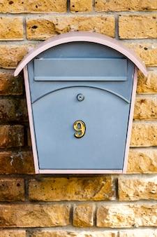 Caixa de correio com o número nove em uma parede de pedra de tijolo amarelo. foto de alta qualidade