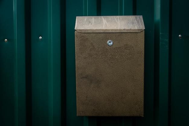 Caixa de correio na cerca de metal verde da folha perfilada.