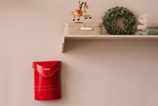 Caixa de correio para papai noel vermelho e prateleira com lembranças de natal no interior da sala de estar