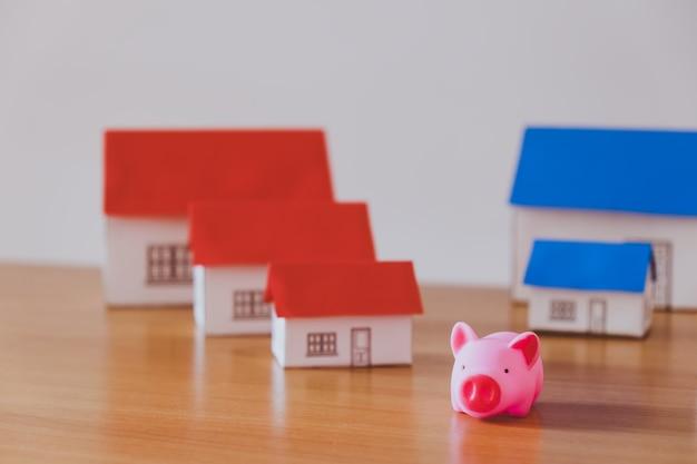Caixa de dinheiro do porco e casa de papel no fundo da parede de madeira