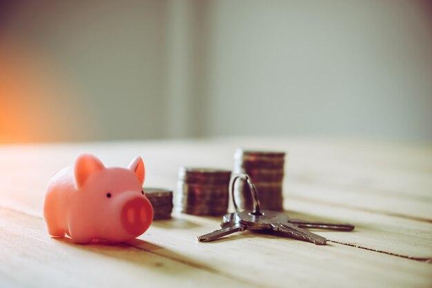 Caixa de dinheiro do porco e chave no fundo da parede de madeira