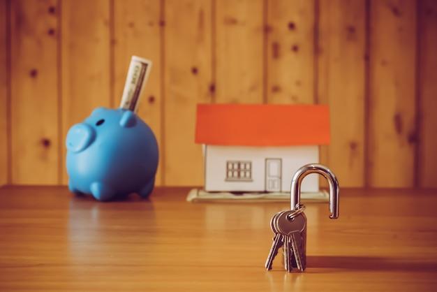 Caixa de dinheiro do porco e decoração de papel no fundo da parede de madeira