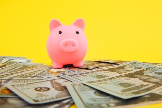 Caixa de dinheiro do porquinho rosa em pilha de notas de dólar em amarelo