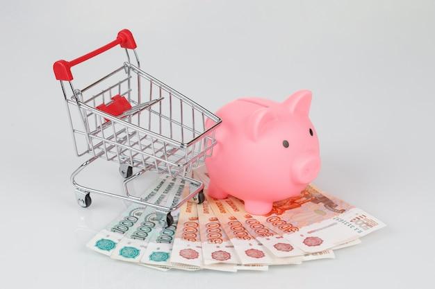 Caixa de dinheiro porquinho rosa na pilha de notas de rublo, conceito