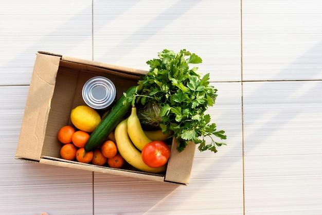 Caixa de doação cheia de mantimentos, frutas e legumes. ver de cima