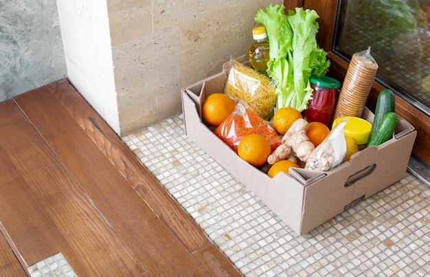 Caixa de doação com alimentos durante a quarentena covid 19. entrega de caixa de comida na porta perto da porta.
