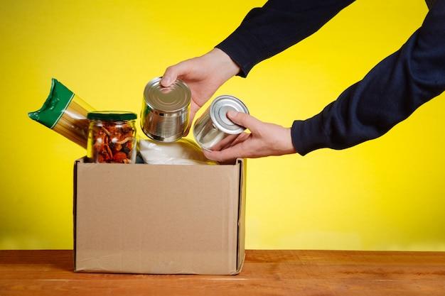 Caixa de doação com comida. e mãos de um voluntário. macarrão, trigo sarraceno, comida enlatada, óleo de enchimento em uma caixa. assistência voluntária aos sem-teto e necessitados. suporte social para as pessoas.
