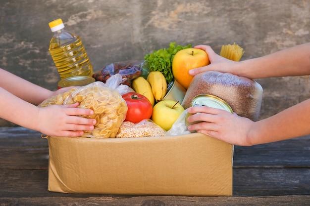 Caixa de doação com comida em fundo de madeira velho.