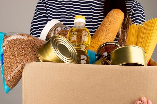 Caixa de doação com comida nas mãos de um voluntário.