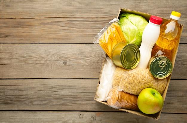 Caixa de doação com comida no fundo cinza de madeira