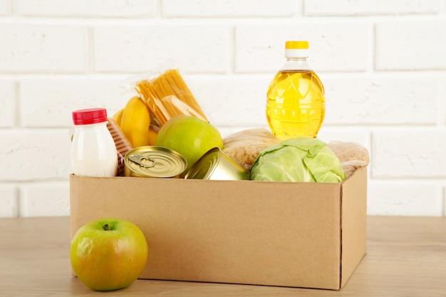 Caixa de doação com comida no fundo da parede de tijolo branco