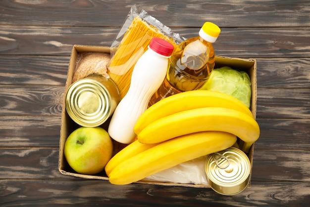 Caixa de doação com comida no fundo de madeira marrom