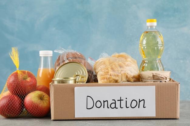 Caixa de doação com diferentes alimentos na mesa cinza. voluntariado
