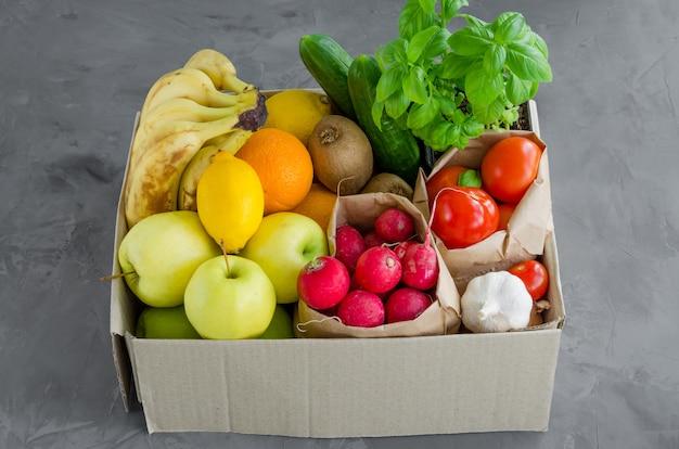 Caixa de doação com frutas orgânicas frescas, legumes e ervas em um fundo de concreto. nutrição apropriada. entrega de alimentos saudáveis para o lar. orientação horizontal.
