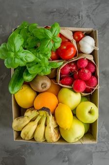 Caixa de doação com frutas orgânicas frescas, legumes e ervas em um fundo de concreto. nutrição apropriada. entrega de alimentos saudáveis para o lar.