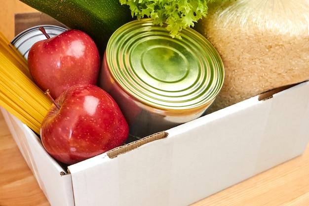 Caixa de doação com legumes, abobrinha, salada, frutas, maçãs, azeite, arroz, macarrão e lata em uma parede de madeira