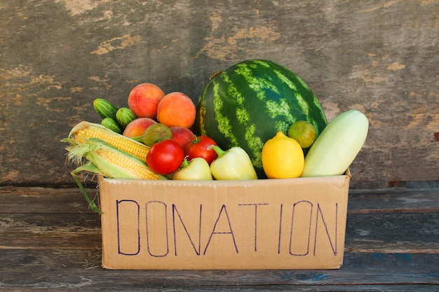 Caixa de doação com legumes e frutas no fundo de madeira velha.