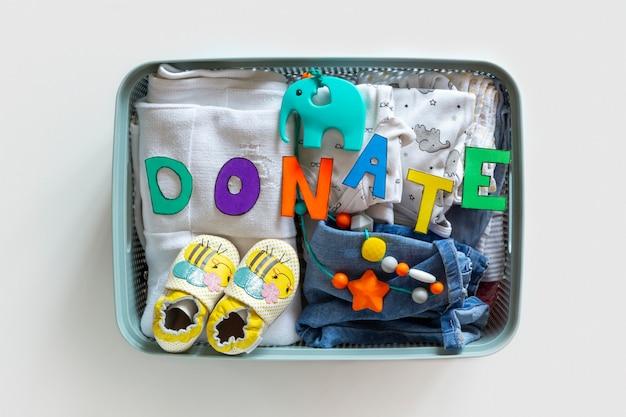 Caixa de doação com roupa neutra unisex do bebê e acessórios de doação em fundo branco. configuração plana