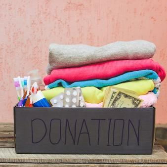 Caixa de doação com roupas, itens essenciais para a vida e dinheiro.