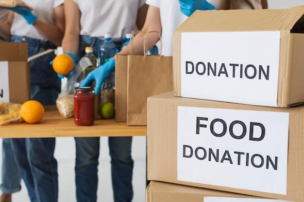 Caixa de doação de alimentos sendo preparada por voluntários com luvas
