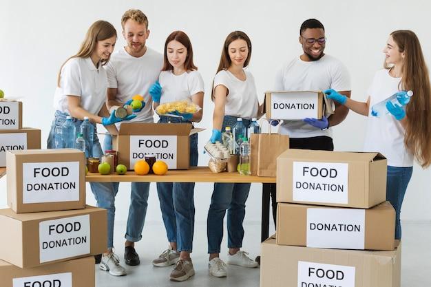 Caixa de doação de alimentos sendo preparada por voluntários sorridentes