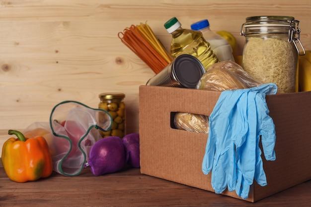 Caixa de doação de coronavírus. caixa de doação com comida e luvas protetoras em fundo de madeira rústica, com espaço de cópia.