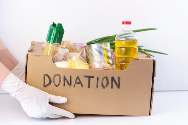 Caixa de doação. nas mãos em luvas de borracha é uma caixa de papelão.