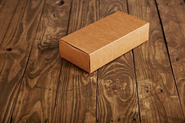 Caixa de embalagem de papelão fechada apresentada em mesa de madeira escovada reforçada, vista lateral, isolada no centro
