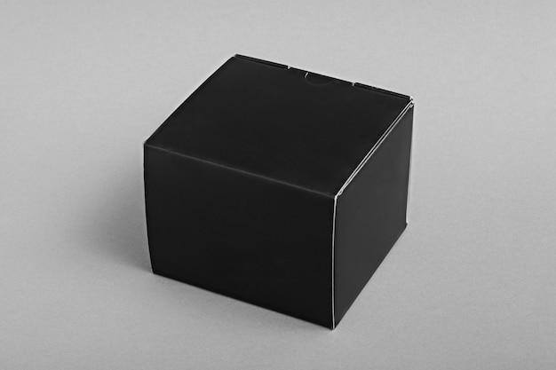 Caixa de embalagem de papelão preta em fundo cinza