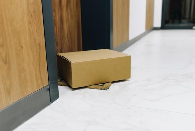 Caixa de encomendas encomendada on-line entregue via entrega sem contato no capacho em frente à porta da frente