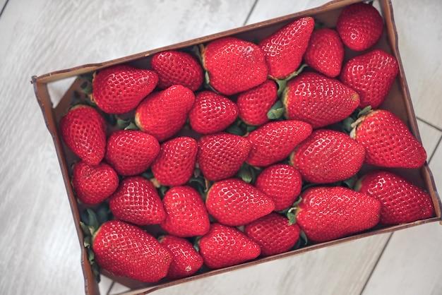 Caixa de enormes morangos vermelhos frescos crus