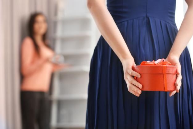 Caixa de esconderijo de mulher com um presente nas costas, close-up