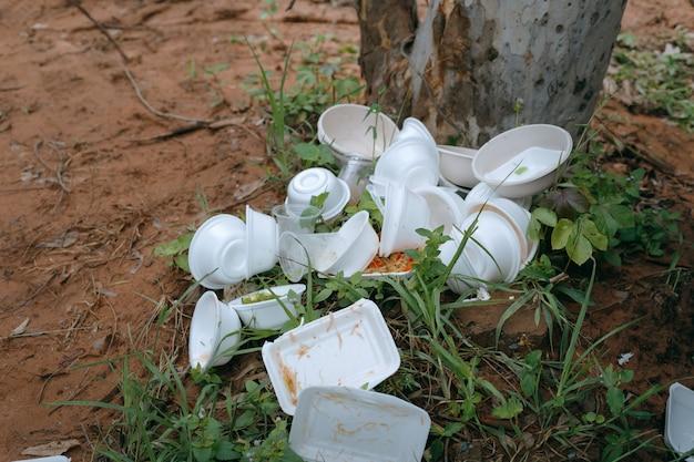 Caixa de espuma de resíduos contendo alimentos usados empilhados no chão no parque
