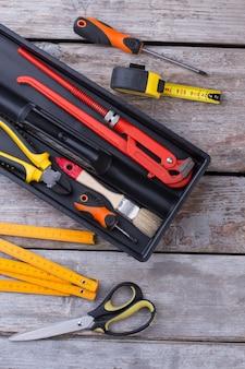 Caixa de ferramentas com diferentes ferramentas em fundo de madeira