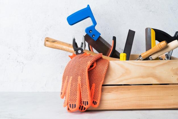 Caixa de ferramentas de madeira de close-up com ferramentas diferentes