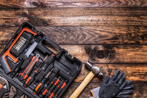 Caixa de ferramentas, martelo e luvas em fundo de madeira