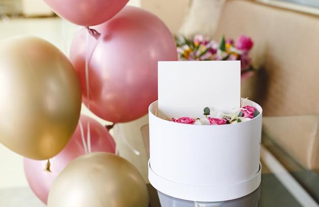 Caixa de flor com cartão em branco de maquete, composição de flores rosas