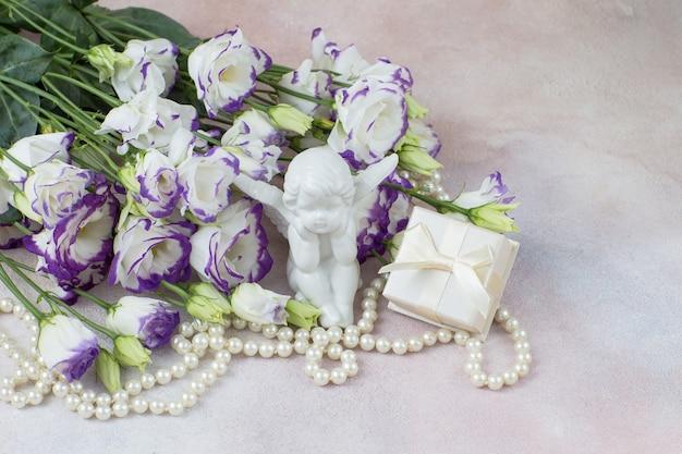 Caixa de flores brancas com estatueta de anjo e pérolas para presente