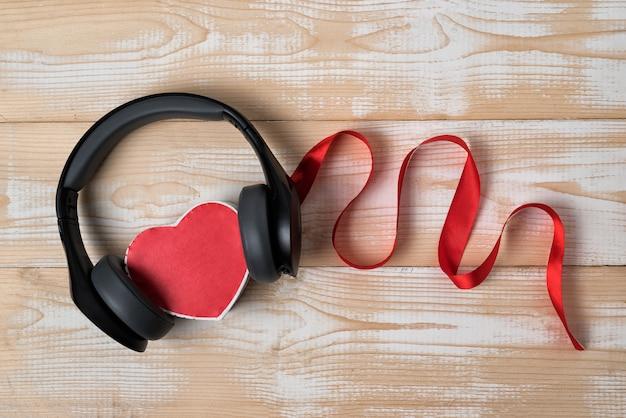 Caixa de forma de coração, fones de ouvido e fita em fundo de madeira. escute o seu conceito de coração. vista do topo
