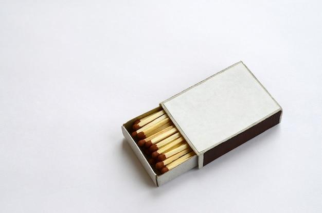 Caixa de fósforos de papelão aberta cheia de fósforos em um fundo branco