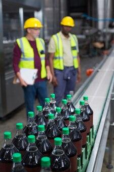 Caixa de garrafas de bebida gelada, movendo-se na linha de produção