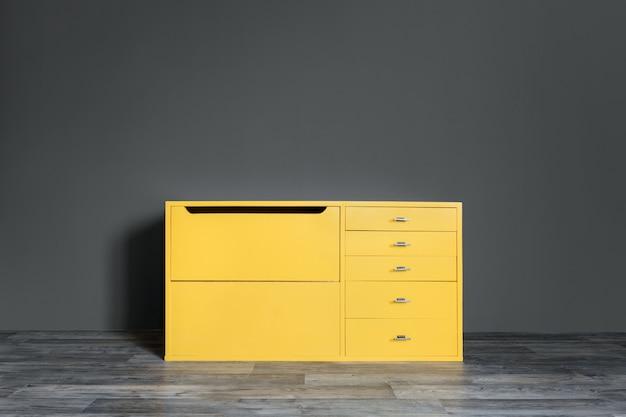 Caixa de gavetas amarela brilhante do vintage na sala perto de uma parede cinzenta escura.