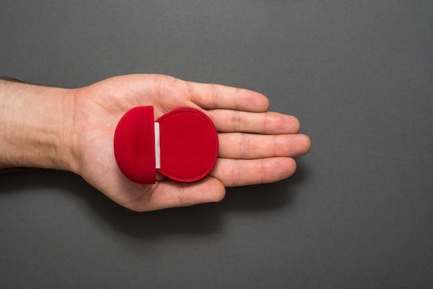 Caixa de joia vermelha aberta vazia na palma da mão masculina. presente. fundo preto. vista do topo