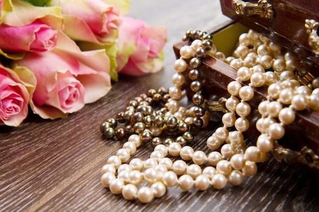 Caixa de jóias com jóias com rosas cor de rosa